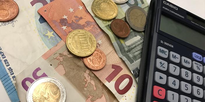 Geldscheine, Münzen und ein Taschenrechner