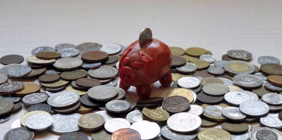 kleines Glückschwein und viele Münzen Sparen
