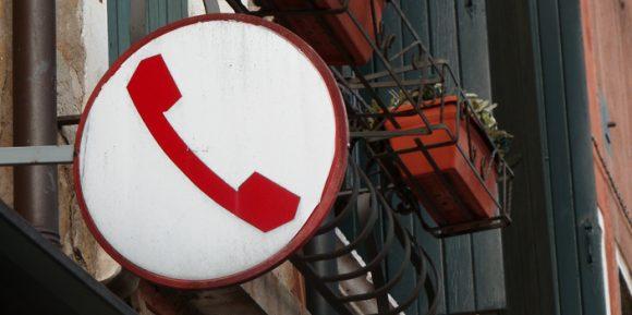 Telekommunikationsrichtlinie Schild mit Telefonhörer an Häuserwand